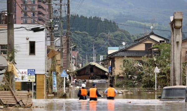 豪雨の影響で水に漬かった熊本県人吉市の市街地。取り残された人がいないか、警察官が拡声器を使い確認していた(4日午後3時49分)=共同