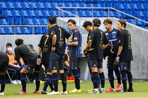 記念のTシャツを着た選手と試合前の写真撮影に臨むG大阪・遠藤ら(4日、パナスタ)=共同