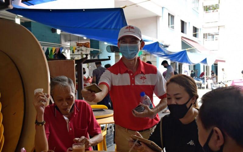 有権者に支持を訴えるシンガポール前進党のレオン・ムンワイ候補(中央の帽子をかぶった男性)