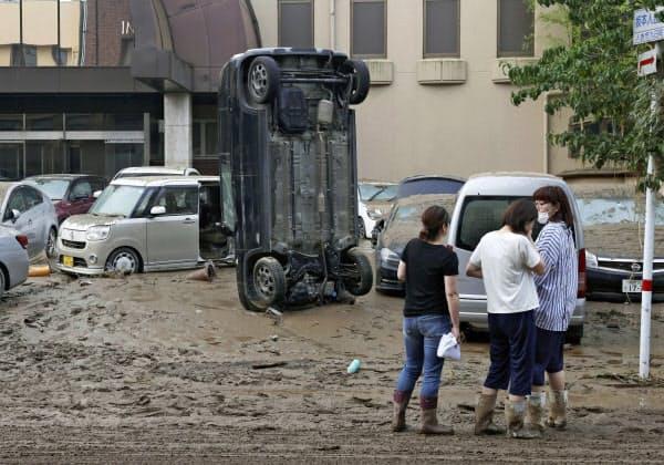 豪雨の影響で流された車(5日午前6時40分、熊本県人吉市)=共同