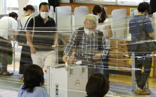 都知事選で投票する有権者。投票箱の前には感染症対策としてビニールカーテンが設置された(5日、東京都新宿区)