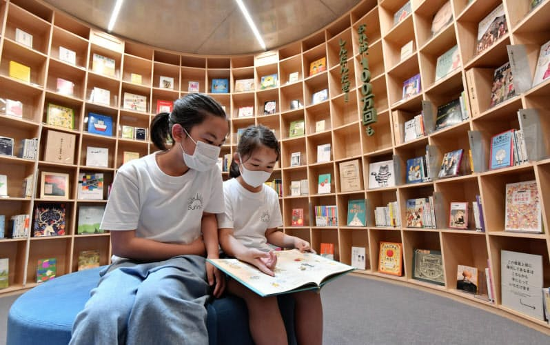 「こども本の森 中之島」で本を手にする女の子(5日、大阪市)=共同