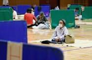 新型コロナウイルス感染防止のため、避難所で間隔を空けて休む女性(5日午後、熊本県八代市)