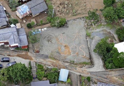 熊本県球磨村で地面に描かれた「米、水、SOS」の文字=5日午前11時49分(共同通信社ヘリから)