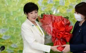 当選を決め、関係者から花束を受け取る小池百合子氏(左)=5日、東京都新宿区