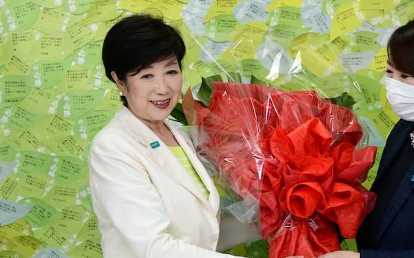 当選を決め、関係者から花束を受け取る小池百合子氏(左)(5日、東京都新宿区)