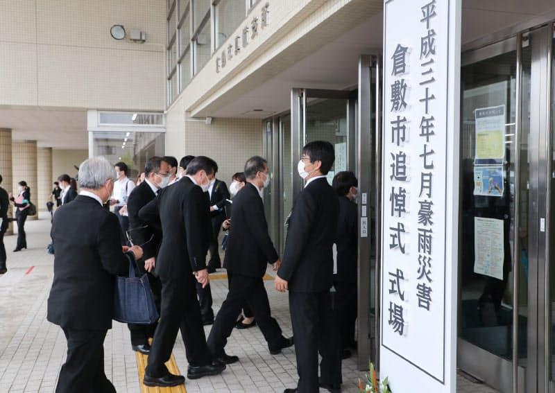 追悼式の会場に向かう人たち(6日午前、岡山県倉敷市の倉敷市真備支所)