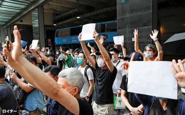 取り締まりを避けるため、白紙を掲げる人たち(3日、香港)=ロイター
