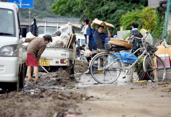 河川が氾濫し住宅に押し寄せた土砂などを片付ける人たち(6日午後、熊本県芦北町)