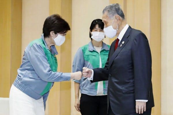 会談を前にグータッチする東京都の小池知事(左)と東京五輪・パラリンピック大会組織委員会の森会長(6日午後、都庁)=共同