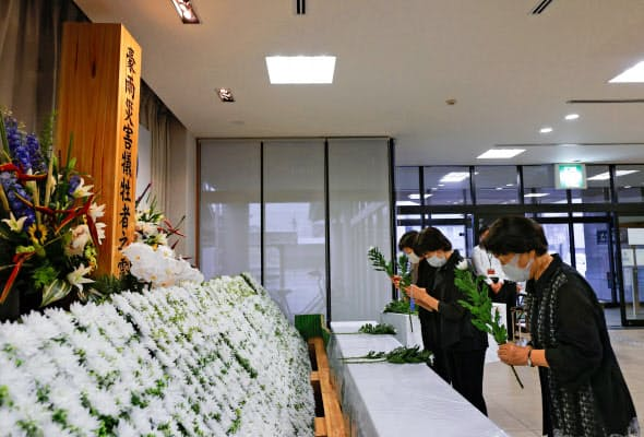 野村町地区の献花台に花を手向ける人たち(7日、愛媛県西予市)=共同