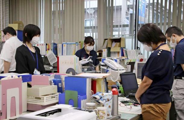 愛媛県大洲市役所で黙とうをささげる職員ら(7日)=共同