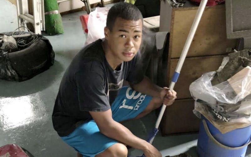 豪雨で浸水被害を受けたジムの復旧作業をする岡沢セオン(7日、鹿児島県鹿屋市)=共同