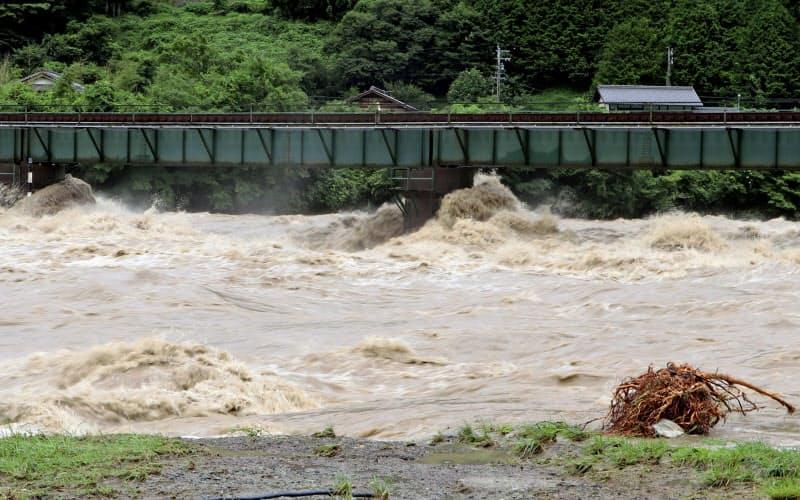 大雨により増水した飛騨川(8日午前、岐阜県下呂市)=共同