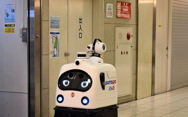 扉の取っ手前で立ち止まり消毒液を拭きかけるZMPのロボット(7日、名古屋市中村区)