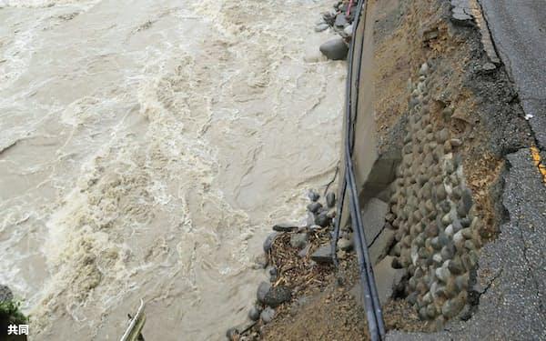 増水した川に土台をえぐられて崩落した、岐阜県高山市の国道(9日)=共同