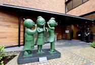 「長谷川町子記念館」の入り口に並ぶ長谷川町子さん(中央)などの銅像。左は「いじわるばあさん」、右は「サザエさん」(9日午前、東京都世田谷区)=共同
