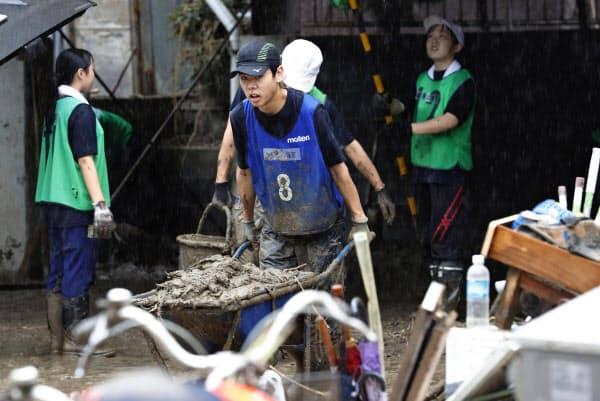 豪雨で被害を受けた熊本県人吉市の住宅から泥を運び出す高校生ボランティア(9日午後0時12分)=共同