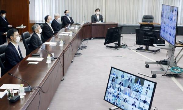 テレビ会議方式の支店長会議に臨む日銀の黒田総裁(左から2人目)ら(9日、日銀本店)