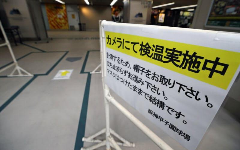 甲子園の入り口に設置された、検温のお知らせ(9日)=共同