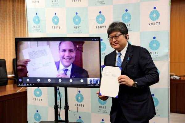 オンラインで会談し、月探査協力の共同宣言に署名した萩生田文科相(右)とブライデンスタインNASA長官(10日、文科省)=代表撮影