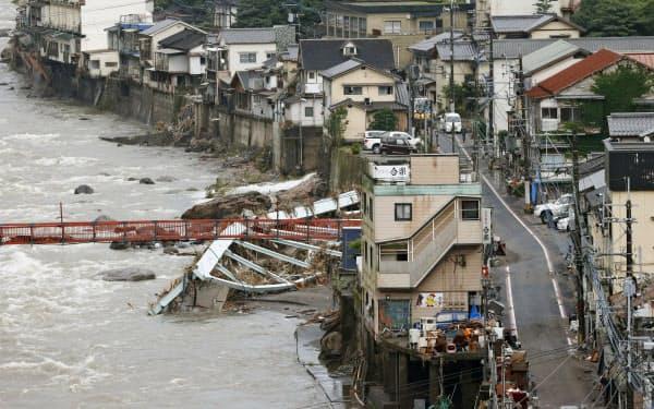 豪雨の被害を受けた大分県日田市の天ケ瀬温泉。玖珠川の増水で流された橋の鉄骨が残る(10日午前)=共同