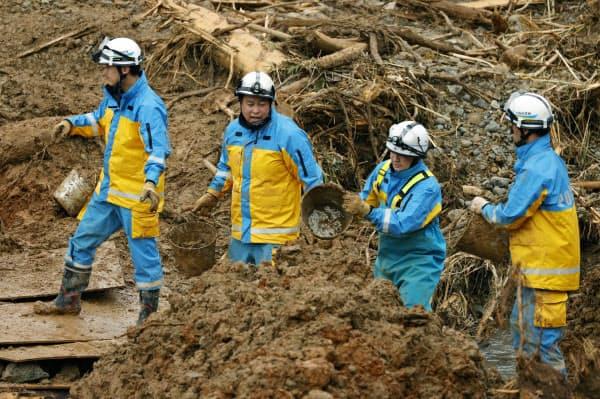 熊本県津奈木町の行方不明者捜索現場でバケツリレーで土砂を運ぶ警察官(10日午前)=共同