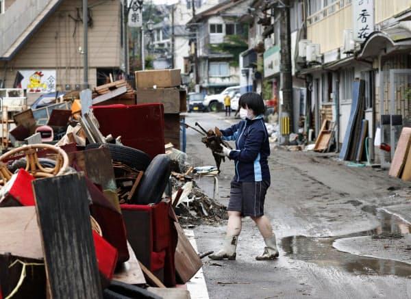 豪雨で被害を受けた大分県日田市の天ケ瀬温泉で、建物内からごみを運び出す女性(10日午前)=共同