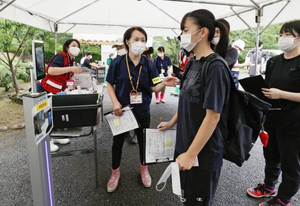 豪雨で被害を受けた熊本県人吉市で始まったボランティアの受付で機器(左)を使って検温する女性(10日午前)=共同