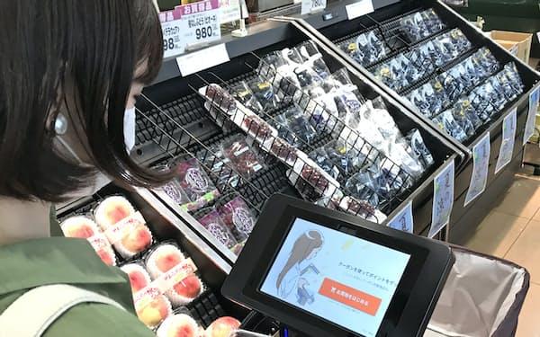 商品を選んで買い物用カートの端末で決済する(北九州市のアルク到津店)