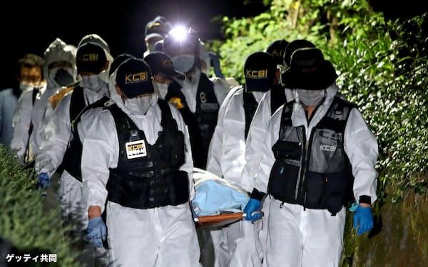 朴元淳ソウル市長とみられる遺体を運ぶ警察当局者ら(10日、ソウル)=ゲッティ・共同