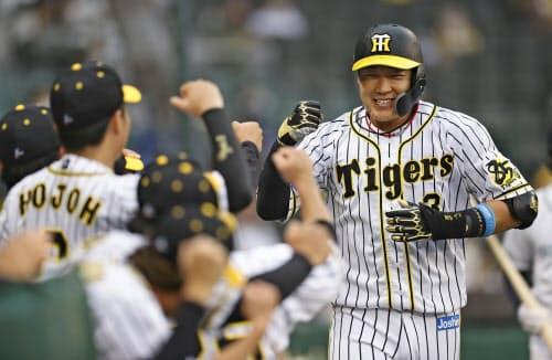 1回、本塁打を放ちナインに迎えられる阪神・大山(10日、甲子園)=共同