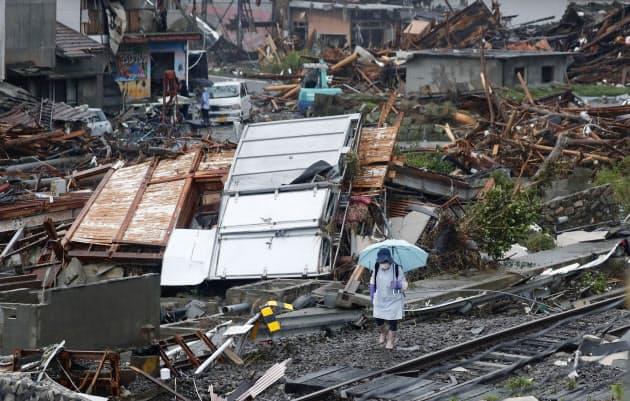豪雨で被害を受けた熊本県球磨村を歩く女性。右下はJR肥薩線の線路(10日午後1時6分)=共同