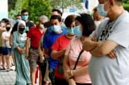 マスクをして投票所に並ぶシンガポールの有権者=ロイター