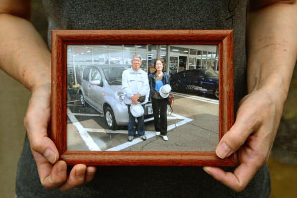 井上三郎さんと節子さんの写真を手にする長女なつみさん(10日、熊本県人吉市)=共同