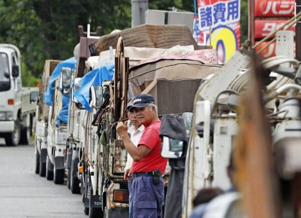 災害ごみ置き場に続くトラックの列(11日午前、熊本県人吉市)=共同