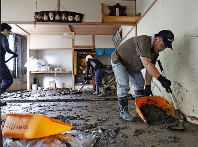 流れ込んだ泥を片付けるボランティア(11日、大分県日田市)=共同