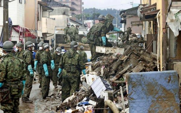 積み重なったがれきなどを片付ける自衛隊員(12日午前8時28分、熊本県人吉市)=共同