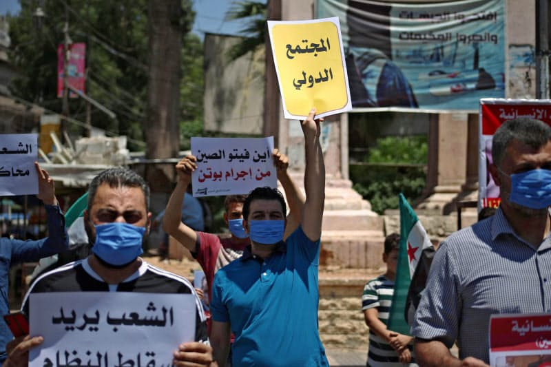 10日、シリア・イドリブで、国連安保理決議案に拒否権を行使したロシアと中国に抗議する人たち=ゲッティ共同