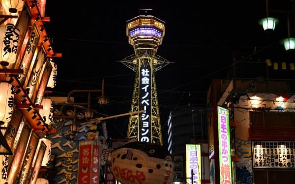 感染状況を判断する大阪府の独自基準「大阪モデル」に基づき、警戒を呼びかける「黄信号」が点灯したことを受け、黄色にライトアップされた通天閣(12日、大阪市浪速区)=笹津敏暉撮影