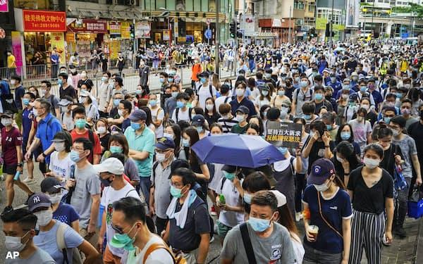国家安全法の施行に抗議しデモ行進する大勢の人たち(1日、香港)=AP