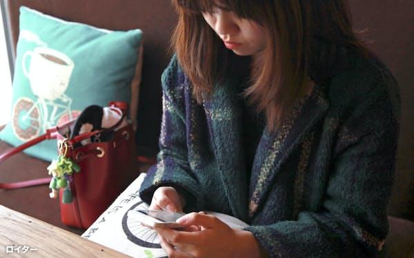 北京のカフェでスマートフォンを操作する女性=ロイター