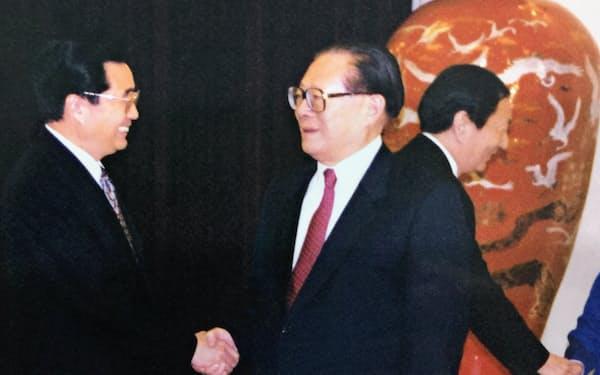 「北戴河会議」で注目されてきた江沢民元国家主席(中)と胡錦濤前国家主席(左)の握手。右後方は朱鎔基元首相(1999年、北京の人民大会堂で)