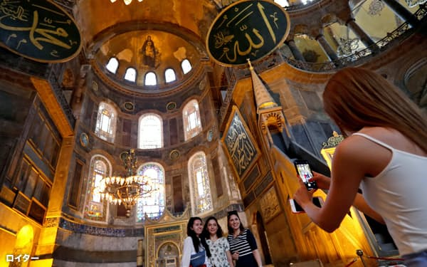 「アッラー」などと書かれた円板の奥にはキリストの絵がみられる(10日、イスタンブール)=ロイター