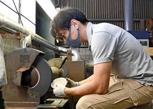 オンラインショップに出品する鉄の小皿を研磨する佐野政製作所の佐野秀充専務(富山県高岡市)=共同