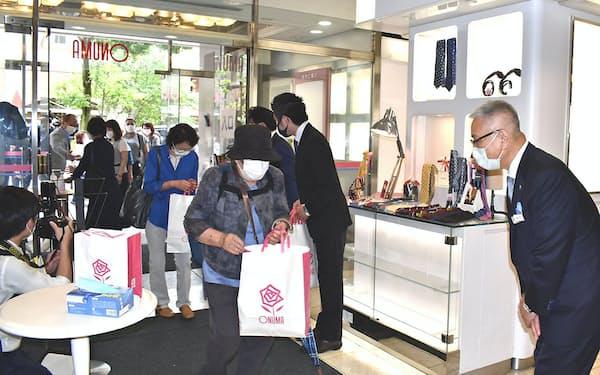 15日、来店客を出迎えるやまきの山下修平会長(右端)