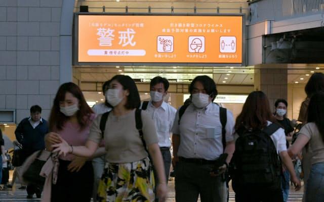 マスクを着けてJR大阪駅前を歩く人たち(15日午後、大阪市北区)