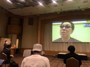 馳氏は北海道から映像中継で会見に参加した(15日、東京都千代田区)