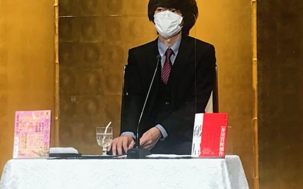 芥川賞に決まった遠野氏はマスクを着けて記者会見に臨んだ(15日、東京都千代田区)