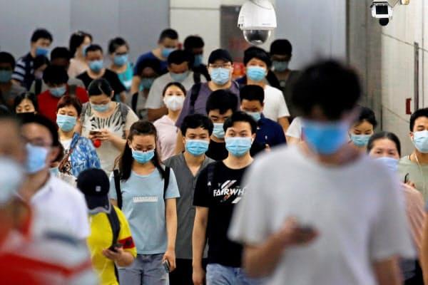 マスク姿で地下鉄駅を歩く人々(14日、北京)=ロイター